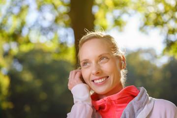 lächelnde frau trainiert mit musik im park