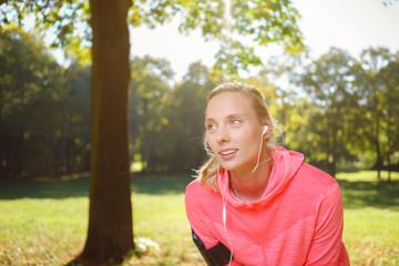 junge frau macht eine pause beim joggen im park