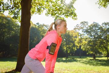 frau dehnt die muskulatur vor dem lauf durch den park