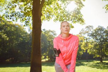 sportliche frau dehnt sich vor dem training im park