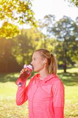 sportliche frau mit wasserflasche beim training im park