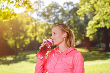 frau trinkt wasser nach dem joggen im park