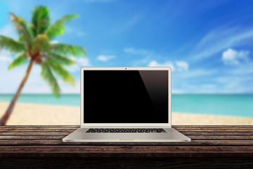 white laptop on the table with a beach palm tree and sea in the background mockup presentation