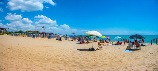 Beautiful vacation beach with beach chairs and sun shades on a sunny day at Lido di Metaponto, Basilicata, Italy