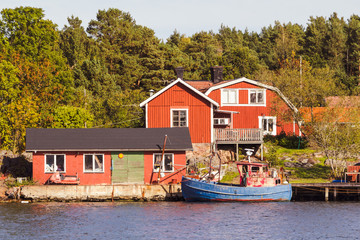 Red cottages and fishing boat in south Sweden