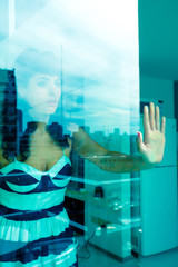 Pensive woman behind a window