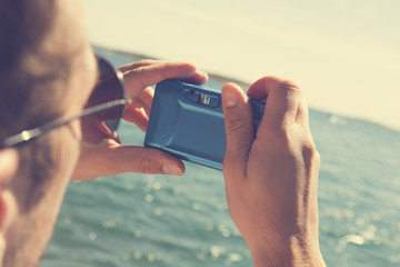 Hipster man taking photos with camera at the beach.