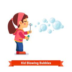Cute little girl blowing soap bubbles through wand