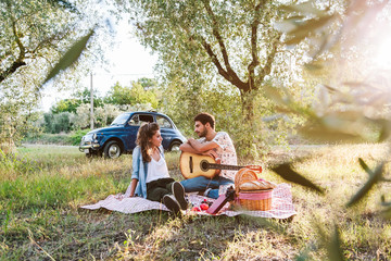 On a beautiful sunny day, a couple of young lovers, makes picnic on grass among olive groves in Tuscany, Italy. Man leans on guitar while talking with his girlfriend. Behind them a blue vintage car