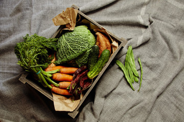 Harvest of vegetables in wooden box with craft paper on rag top