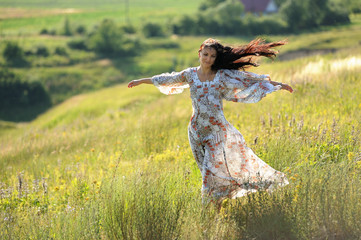 Long haired slender girl in light dress on the hill in windy sum