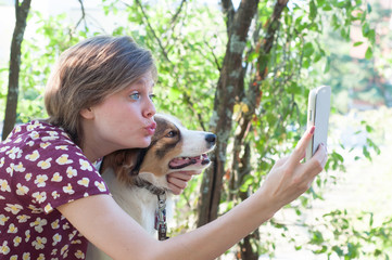 blonde girl with his dog and his smart phone
