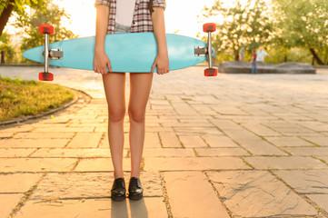 Overjoyed girl holding skateboard