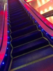 Colorfully lit escalator steps.