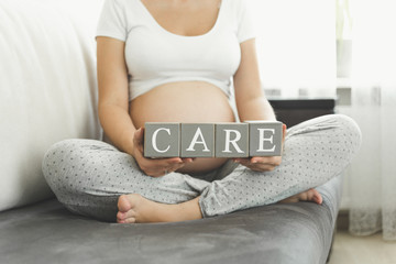 Closeup of pregnant woman holding letters making word Care