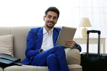 Business man with suitcase and tablet sitting on sofa at home