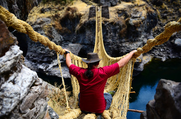 Traveller and dangerous rope bridge