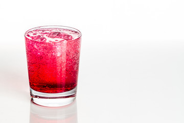 Refreshing red fizzy soft drink with ice in transparent glass