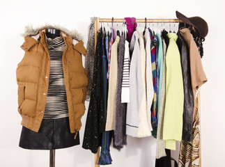 Wardrobe with clothes arranged on hangers and a winter outfit on a mannequin.Dressing closet with autumn clothes and accessories. Tailor's dummy wearing a winter vest with leather skirt.