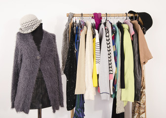 Wardrobe with clothes arranged on hangers and a winter outfit on a mannequin.Dressing closet with autumn clothes and accessories. Tailor's dummy wearing a fluffy grey sweater with scarf and hat.