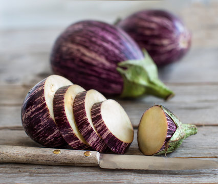 Fresh Raw striped eggplants and slices with knife