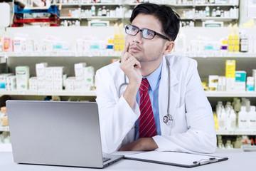 Pensive pharmacist in the drugstore