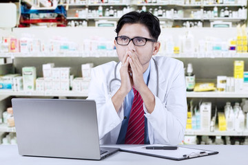 Thoughtful pharmacist sitting in the drugstore
