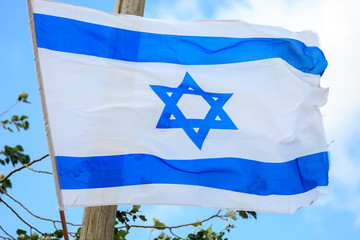 Blue and white flag of Israel over the sky
