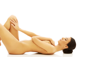 Woman lying on the floor covering breast