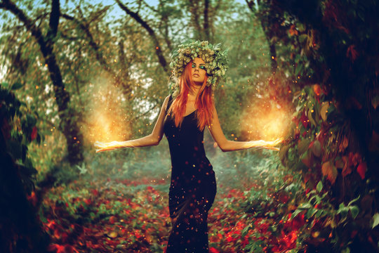 Elegant redhair girl witch conjures in the magic forest