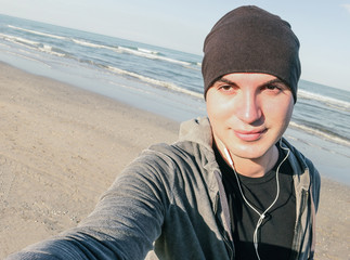 Young handsome guy with male sport clothes taking selfie on the beach in autumn season -  Healthy lifestyle and fitness training concept - Tilted horizon - Vintage desaturated filter look