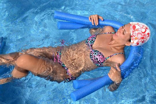 joven mujer en la piscina haciendo acua gym, gimnasia de agua.