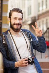Attractive bearded man is photographing in town