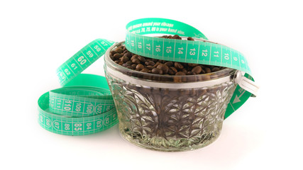 Coffee and Weight Loss: Coffee beans in a glass bowl with a tape measure on a white background