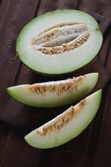 Sliced cantaloupe melon over dark rustic wooden surface, closeup
