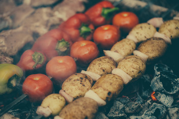 Meat and vegetables are roasted on coals