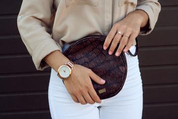 Trendy girl holding small brown leather bag handbag