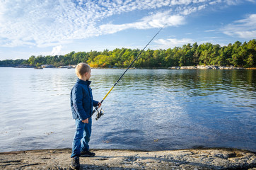 Small boy with big fishing rod