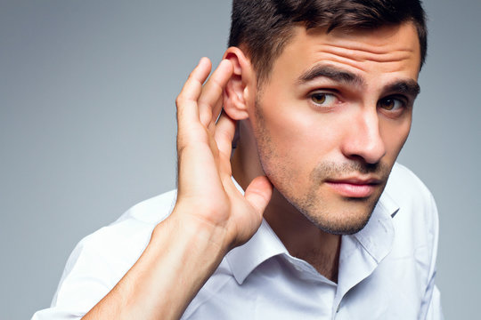 Young businessman holds his hand near ear.Close up portrait