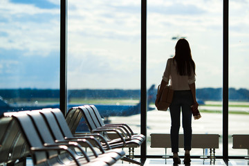 Young woman near window in an airport lounge waiting for flight
