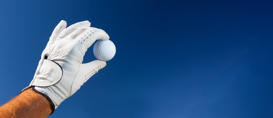 Deurstickers Golf Hand wearing golf glove holding a white golf ball - large copy space on the right