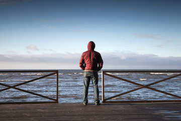 Young man in hood looking on the sea from pier