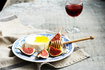 Plate with brie cheese, honey and figs and glass of wine