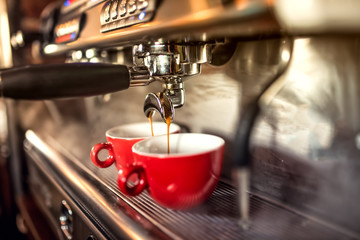 coffee machine preparing fresh coffee and pouring into red cups at restaurant, bar or pub.