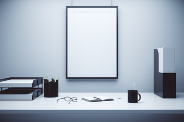 Blank picture frame on a wall and table with glasses, diary and