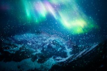 Snow falling against aurora borealis - focus on snowflakes
