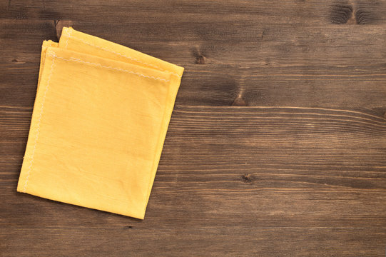 Yellow napkin at left of wooden background
