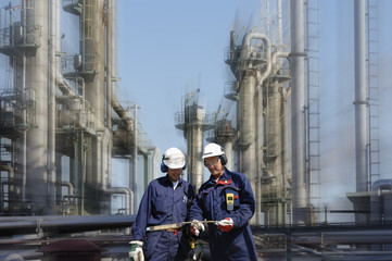 oil and gas industry with two refinery workers in foreground