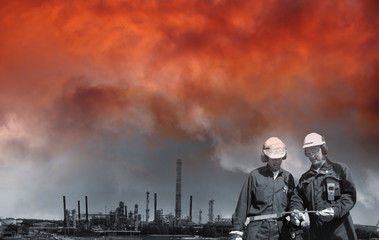 oil and gas industry with a red sunset sky and smoke, two workers in foreground