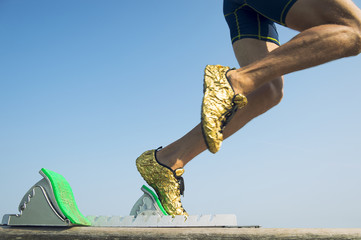 Athlete wearing gold running shoes takes off in a blur from from the race track starting blocks